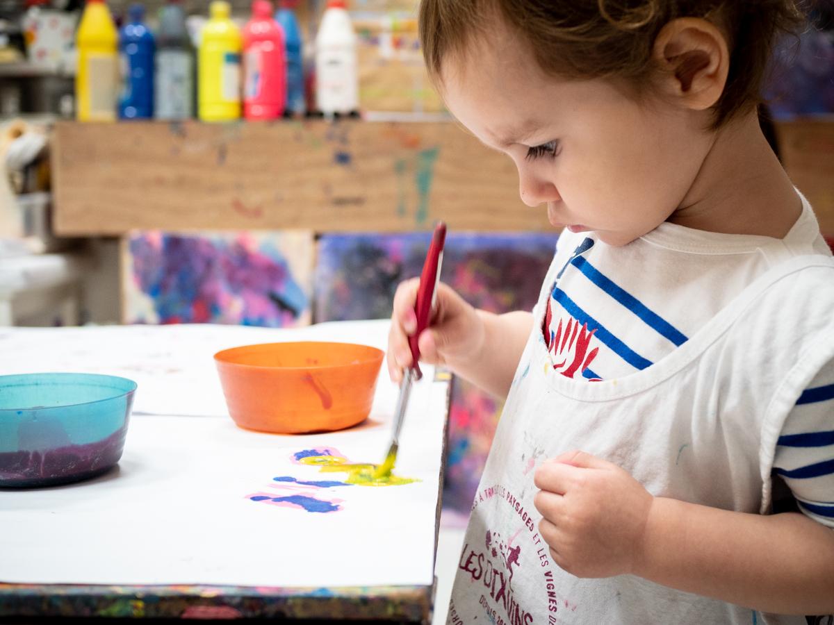Un enfant concentré sur sa peinture en atelier KID & Sens à Aix en Provence